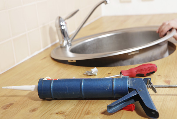 Caulking gun with silicone sealant against kitchen sink installation process